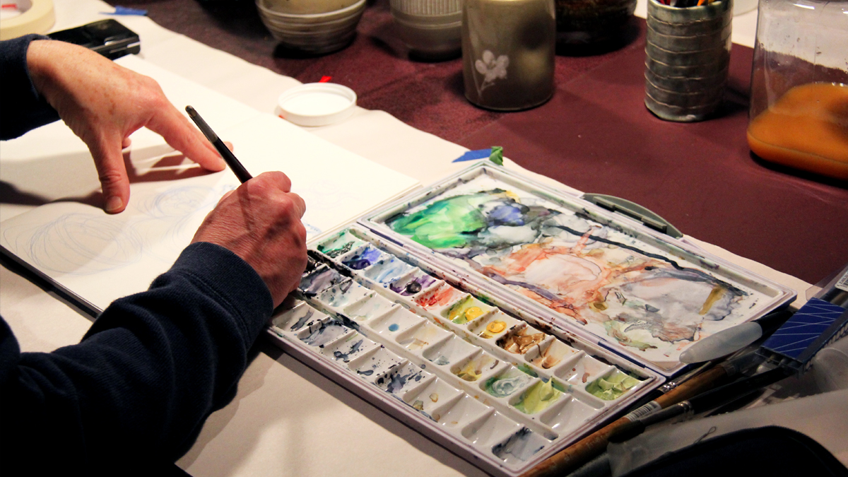 Person painting using watercolours