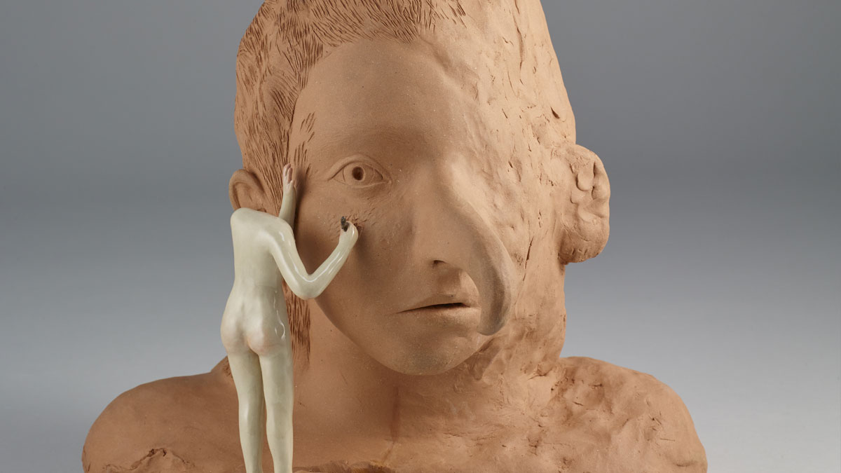 Headless figure sculpting a large clay bust