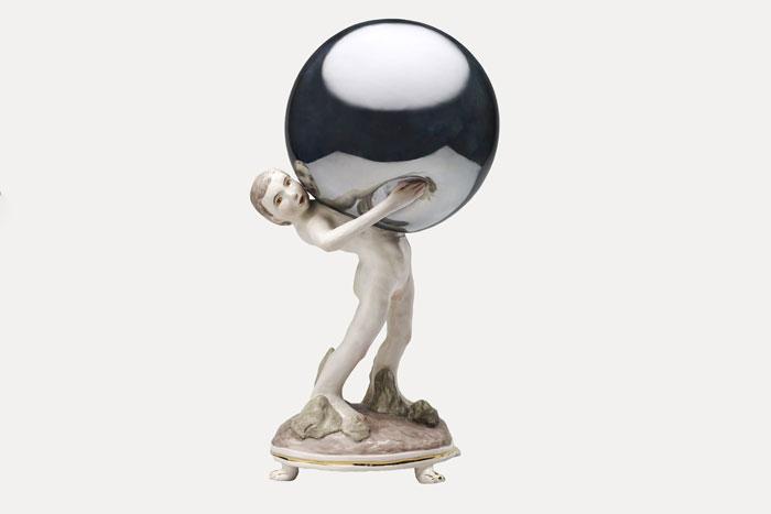 Ceramic figure of a boy holding a mirrored globe
