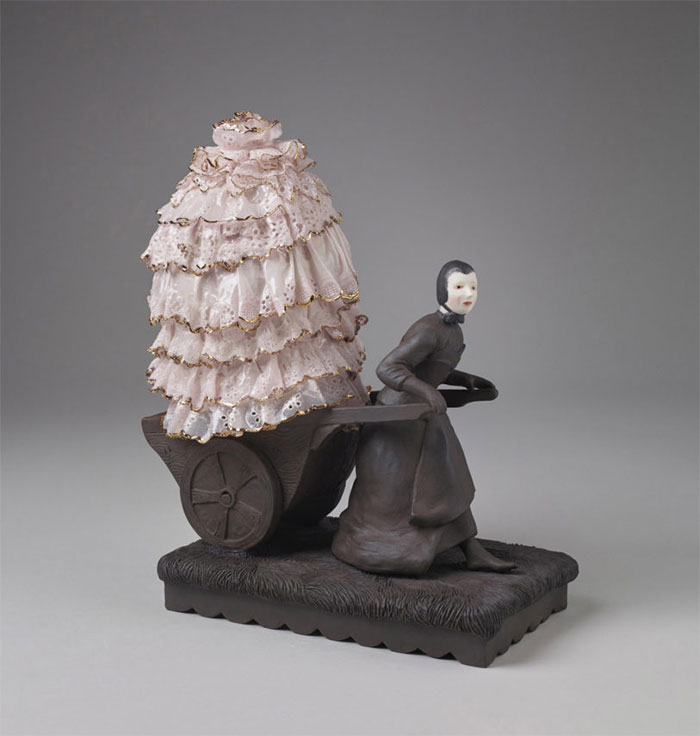 Porcelain figure pulling a wheelbarrow containing a lace dress