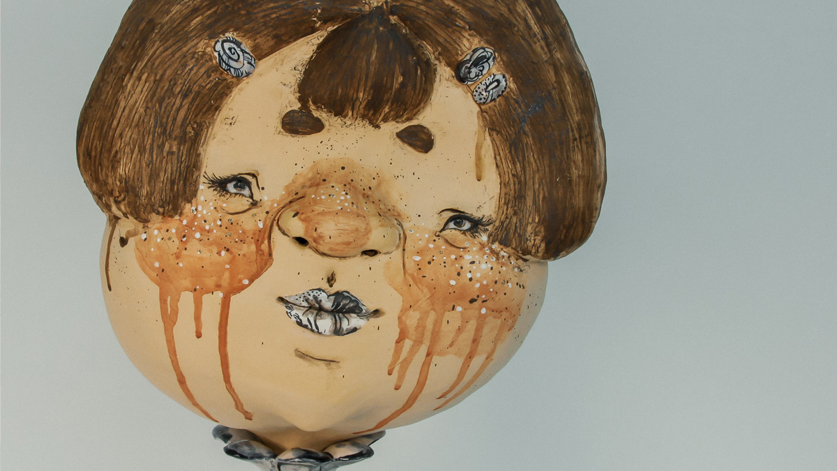 Ceramic sculpture depicting the head of a young girl or doll