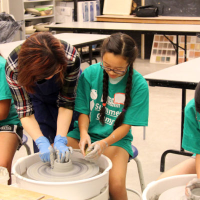 Campers working on the pottery wheel