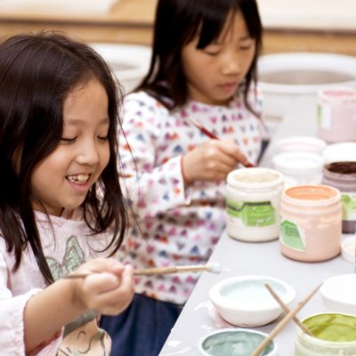 Two girls mixing clay glaze