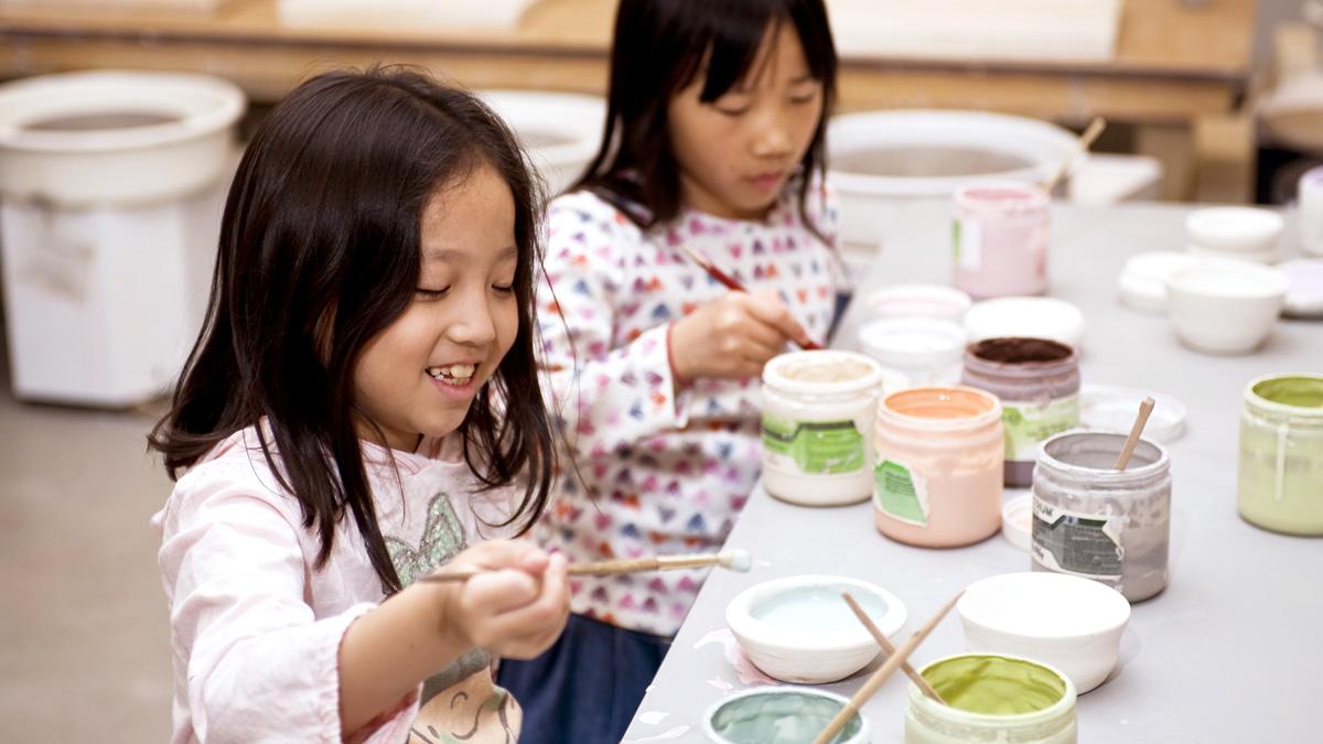 Two girls mixing clay glaze