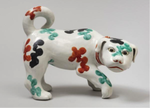 A ceramic dog with red, blue, and turquoise flowers painted on it