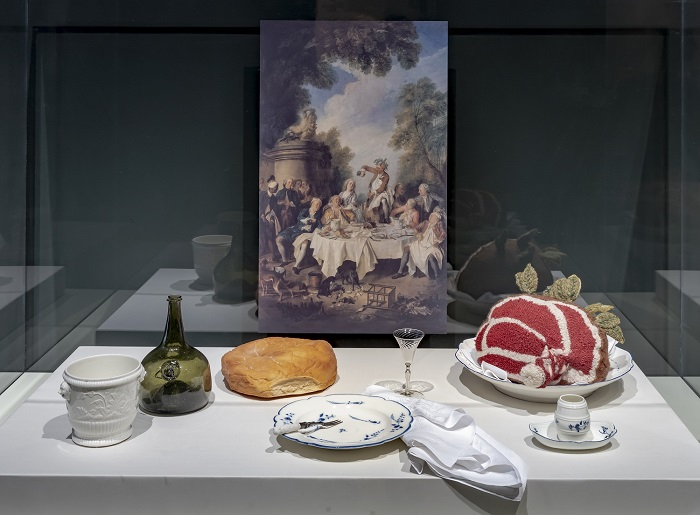 A recreation of an 18th century dinner featuring roast beef, bread, serving plates, and a wine decanter. A painting of a dining scene is in the background
