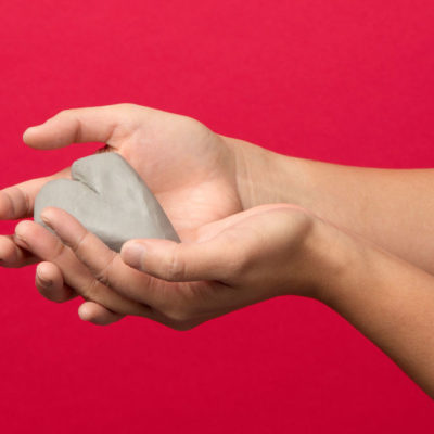 Hands holding clay heart on red background