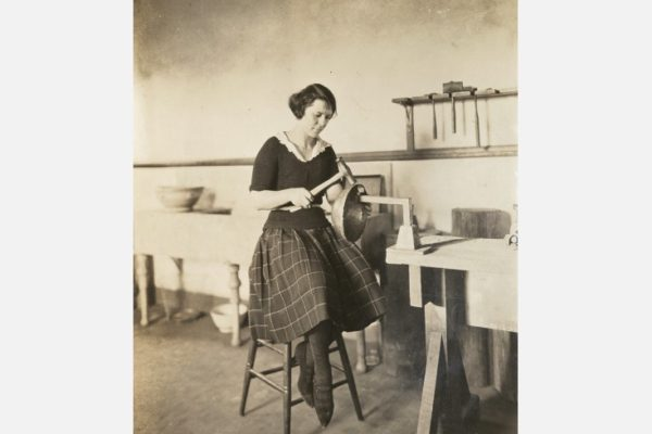 Newcomb College student forming a metal bowl, c. 1920, Newcomb Art School Scrapbook, University Archives, Tulane University