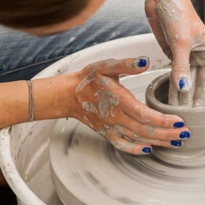 Student throwing on the pottery wheel