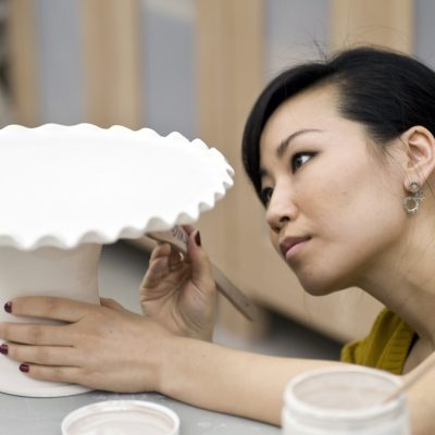 Woman working on a ceramic cake stand