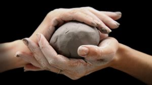 Hands holding a ball of clay
